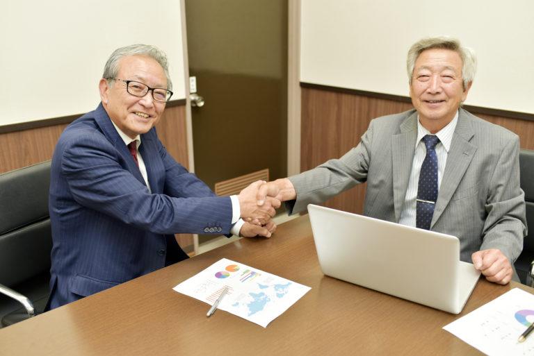 会議室で握手するシニアビジネスマン